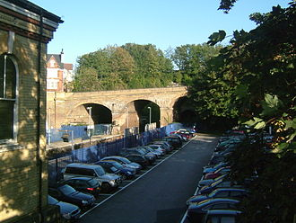 Chatham railway station - This 2007 photo, facing east and showing the Chatham Tunnel and Maidstone Road bridge, clearly illustrates the effect of the Kent Coast Electrification Scheme. Loop platforms existed either side of the mainline platforms, with the London bound loop being situated in the foreground where one of the car parks is currently.