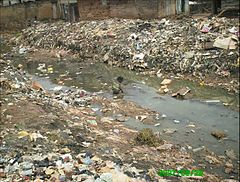 Child defecating in the open in a canal in the slum of Gege in the city of Ibadan, Nigeria