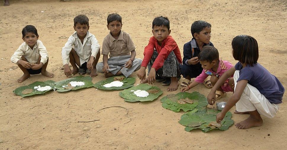 Children eating kheer and puri, Chambal, India
