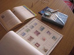Chilean stamp album and catalogue, and a magnifying glass.jpg