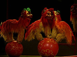 Chinese variety art - Human Lion balancing on a globe. Each lion suit usually has two performers.