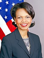 Condoleezza Rice wearing a dark blue jacket over a patterned blouse. The United States flag is in the background.