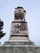 An image of a relief on the monument's top block representing either Fame or an angel placing a laurel wreath upon the head of a dying soldier clasping his sword
