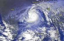 Image of a cyclone whose center is slightly above center. The storm's clouds appear white with a bluish tinge. An eye is visible in gray shades at the storm's center. While the thicker clouds are opaque and clustered around the cyclone's center, sprawling, transparent clouds span the length of the image.