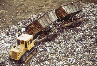 Fresh Kills Landfill - A D7 Tractor with two Athey Wagons dumping, 1973.