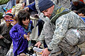 Defense.gov News Photo 110201-F-2185F-303 - U.S. Army Sgt. 1st Class Manuel Delarosa finds a pair of shoes for a young girl while helping Afghan National Security Forces distribute winter.jpg