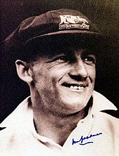 A man wearing a black shirt, with the collar up, and a dark cap with a light-coloured emblem
