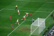 Vue de huit joueurs se disputant le ballon devant le but et de l'arbitre pendant un match de football