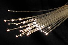 A bunch of pale yellow semi-transparent thin strands, with bright points of white light at their tips to one end.