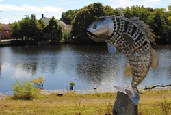 A sculpture of a fish in a park on the banks of a river.
