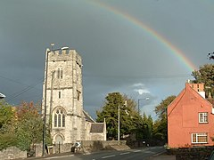 Three stage square stone church tower on the left. Red painted building on the right and a rainbow.
