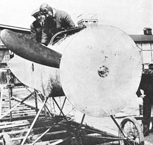"Synchronization gear - Fokker Synchronization gear set up for ground firing test. The wooden disc records the point on the disc of the propeller where each round passed. The diagram opposite shows the probable result for a properly working gear. Inherent inaccuracies in both the gear and the triggering of the gun itself, small faults in normal service ammunition, and even the differing RPM rates of the engine, all combine to produce a ""spread"" of hits rather than every bullet striking the disc in precisely the same spot."