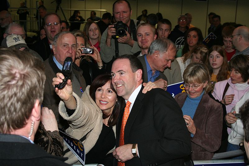 Former Arkansas Governor and 2008 Republican presidential candidate Mike Huckabee with a supporter at a campaign rally in Wisconsin.jpg
