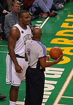 A basketball player stands on a basketball court. He wears a green jersey with the word «CELTICS» and the number 11 on the front.