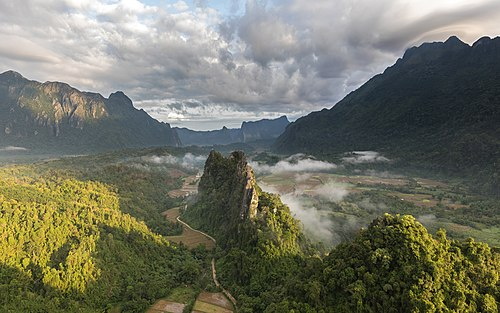 Green karst peaks seen from the top of Mount Nam Xay a sunny morning during the monsoon Vang Vieng Laos