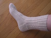 A hand knitted white lace sock made out of han...