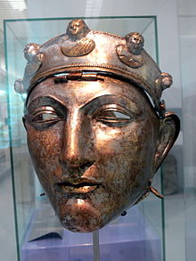Colour photograph of the Nijmegen helmet, which like the Emesa helmet is silver and has a face mask shaped like a human face. It hangs by a central hinge from a brow band, which is decorated with five raised busts: three of female figures, and two of male figures.