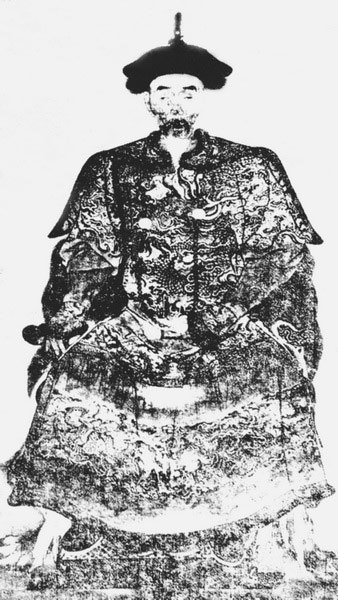A full face black-and-white portrait of a sitting man with a gaunt face, wearing a robe covered with intricate cloud and dragon patterns.