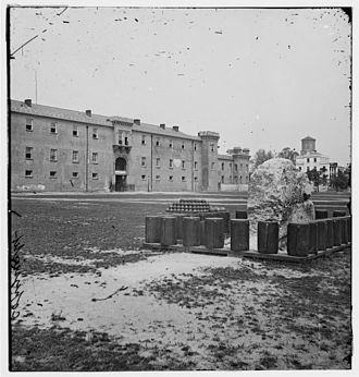 Marion Square - In this 1865 photo of the original Citadel building, a remnant of the city's defensive wall, known as a horn work, is visible in the foreground; the horn work is still in place in 2014 surrounded by a low iron fence.