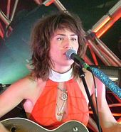 Head-and-shoulders colour photograph of Joan Wasser singing live in 2006. She is playing a guitar and singing into a microphone.