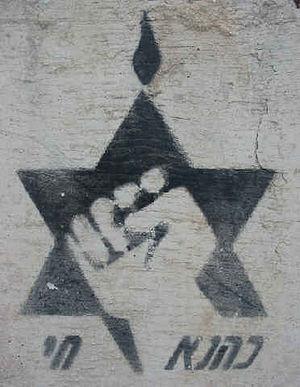 "Kach and Kahane Chai - Kach logo spraypainted on a cement block reading ""Kahane Chai"""
