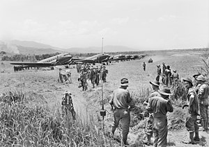 A line of Dakotas on a grass airstrip. Men wearing slouch hats file off a plane. A jeep drives along the strip. Other men in uniform and civilians look on.