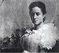 Kaiulani seated in light dress, hands holding book in lap facing left (black and white, close crop).jpg