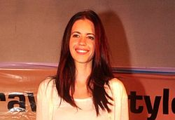 Koechlin in a white dress smiling at the camera