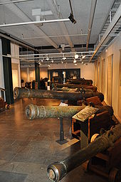 Photograph of an exhibition hall with several types of bronze cannons on naval gun carriages