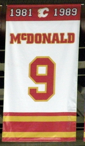"A white, rectangular banner with red and yellow trim at the top and bottom. It reads ""1981–1989 McDONALD 9"""
