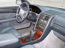 Automobile front interior, passenger side, showing dashboard, wood center console, and leather trim.