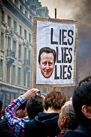 2011 London anti-cuts protest - A placard accusing David Cameron is held up in front of a pall of smoke in Oxford Street