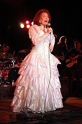 An older woman with long brown hair wearing a long white dress, singing into a microphone