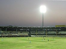 A cricketer bowling in front of largely empty stands. A single lit floodlight is visible in the background. Other cricketers can also be seen batting or fielding on the ground.