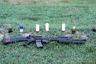 M203 grenade launcher - An M16A2 rifle equipped with an M203 grenade launcher lies in the grass near some of the types of 40 mm ammunition available for use with the M203. The cartridges are, from left to right, multiple projectile, practice, green star flare, white star flare, red star flare and high explosive dual purpose.