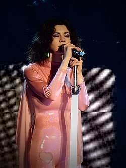 A young brunette woman in a long-sleeved pink dress, singing into a microphone