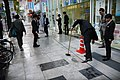 Men in suits sweeping sidewalk Osaka.jpg