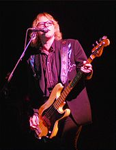 Mike Mills ludas basgitaron kaj kantas en mikrofonon portante Nudie-proceson