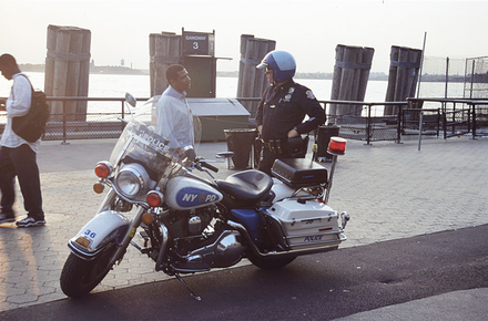 Motorcycle police officer speaks with a passerby NYPD police motorcycle.png