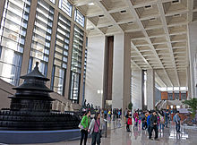 A large whitish interior space with a very high ceiling lit by many windows on its left stretches off into the far background. There are people walking around within. At left in the foreground is a large dark wooden model of a round three-tiered pagoda