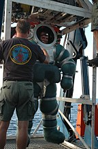 A diver in an armoured diving suit stands on a launch and recovery platform on the support vessel, attended by a crewman.
