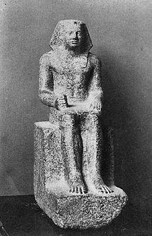 Small statue showing a king seated, wearing the nemes and clenching his right hand.