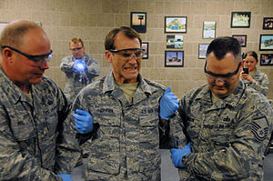 Taser - Master Sgt. Eric Johnson, of the 119th Wing public affairs office, center, reacts to the painful effects of a Taser electronic control device (ECD) shot into his back by Capt. Joseph Anderson, the 119th Security Forces commander, Oct. 17 as Master Sgt. Jarrod Pahl, left, and Master Sgt. Steven Gibson support him for safety reasons at the North Dakota Air National Guard, Fargo, N.D.