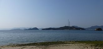 Ōkunoshima - Ōkunoshima seen from the island of Ōmishima, in the southeast. The pylon on the right is 226 metres high, the tallest in Japan.