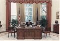 Photograph of President Reagan working at his desk in the Oval Office - NARA - 198593.tif