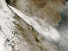 Volcanic ash streams out in an elongated fan shape as it is dispersed into the atmosphere.