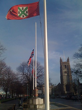 Flag of Plymouth - Plymouth flag alongside Union Jack at Plymouth Guildhall, with St Andrews Church visible in background