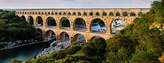 Aqueduct (water supply) - The multiple arches of the Pont du Gard, in Roman Gaul. Its lower tiers carry a road across the river, and the upper tiers support an aqueduct conduit that carried water to Nimes