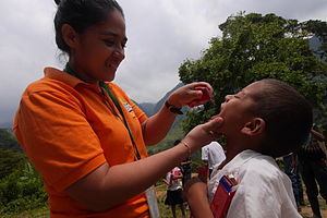 Catacamas - Aury Navarro, a Nursing Assistant with Predisan, pours a fluoridated rinse into the mouth of child in the rural mountain village of Esperanza in the Sierra Agalta Rainforest near Catacamas, Honduras.