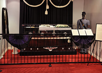 Coffin - Recreation of President Abraham Lincoln lying in repose in replicated coffin at the National Museum of Funeral History, Houston TX, with a police man standing guard.